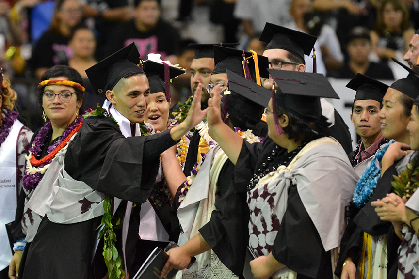 Student hi-fiving at commencement