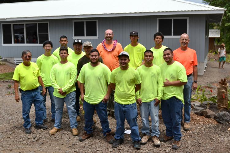 Group photo of carpentry students outside house they built