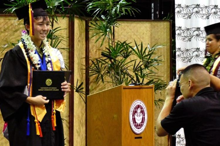 Craig Okahara-Olsen with his degree at commencement